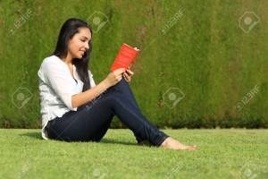 21282580-Sch-ne-arabische-Frau-liest-ein-Buch-sitzt-auf-dem-Rasen-eines-Parks-mit-einem-gr-nen-Hintergrund-Lizenzfreie-Bilder
